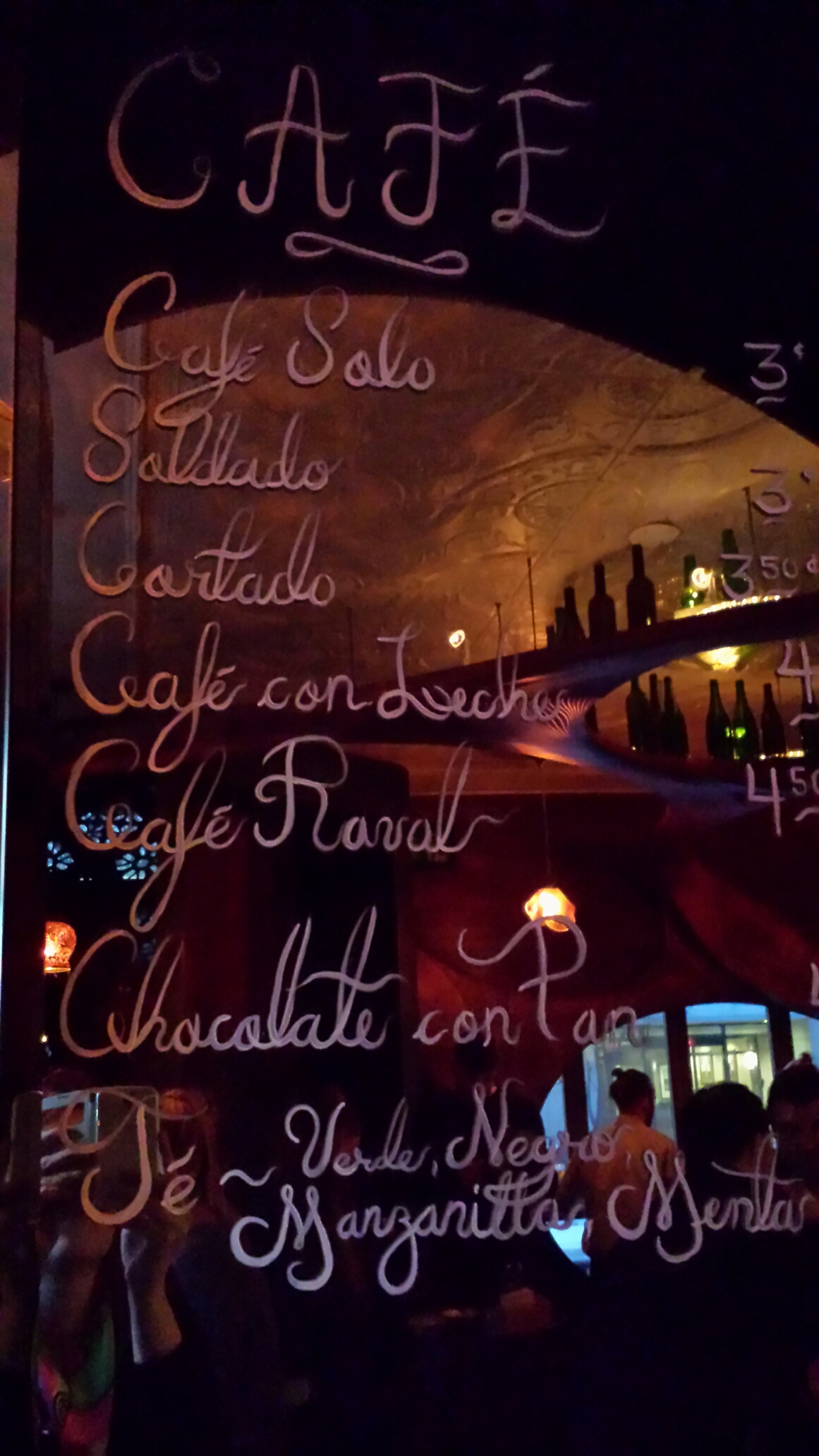Menu of coffees written in cursive on a mirror