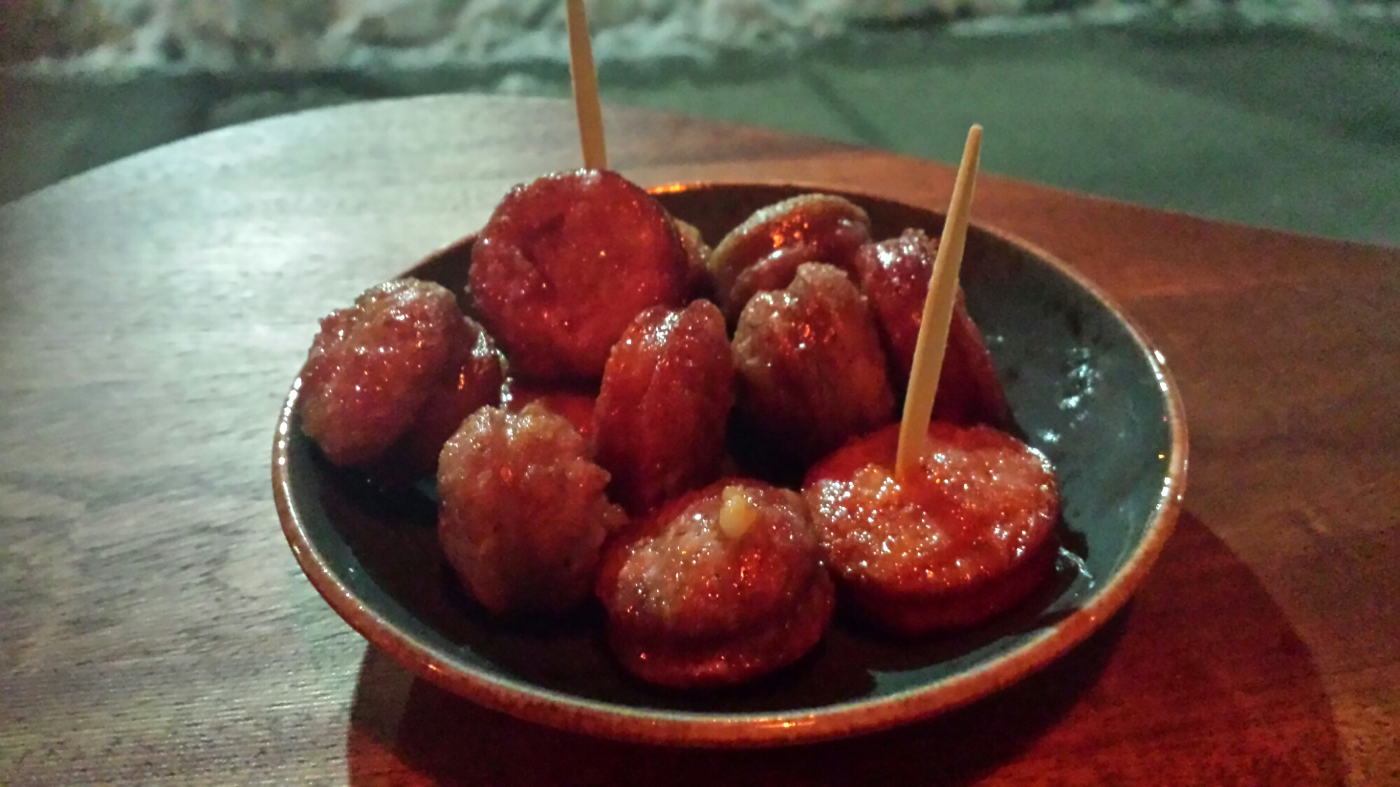 A bowl of sausage pieces with toothpick sticking out